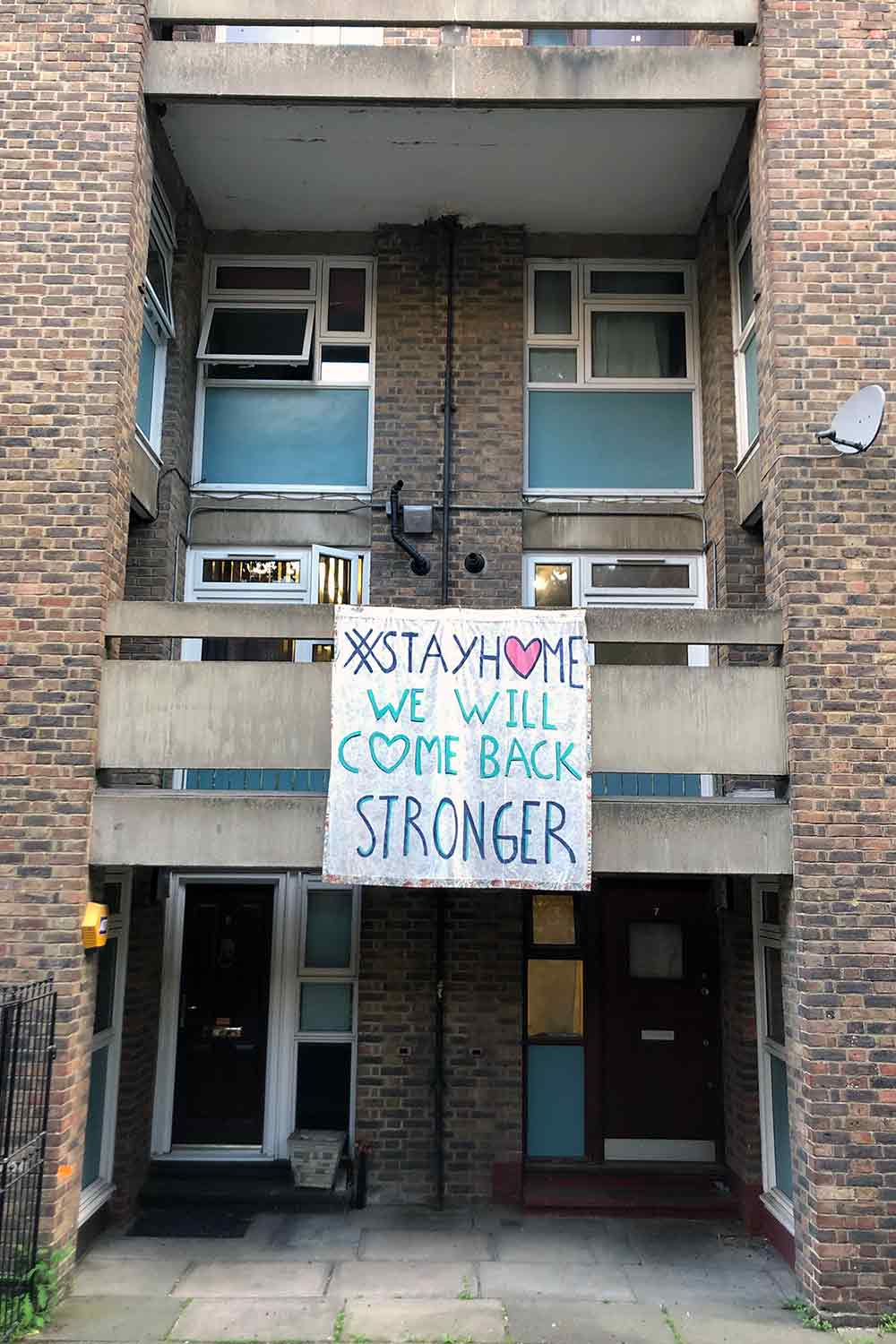 Sign hung on building saying 'Stay Home, We Will Come Back Stronger'