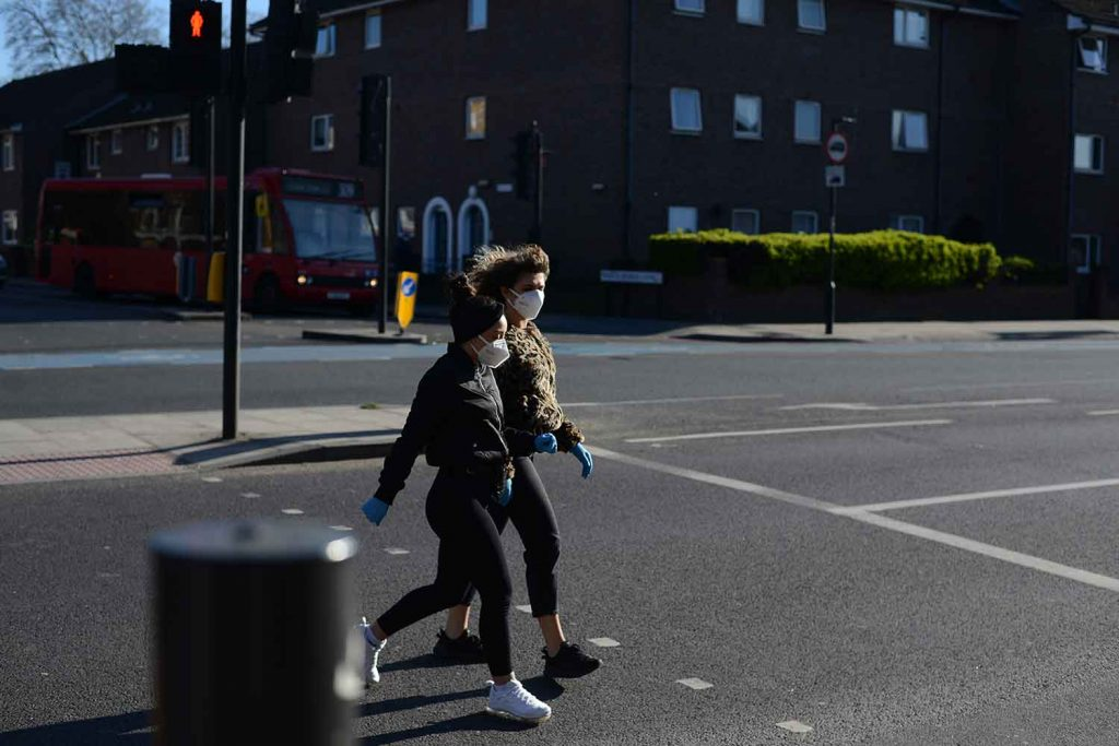 Two women crossing the road wearing masks photographs of Bow in lockdown by Matt Payne