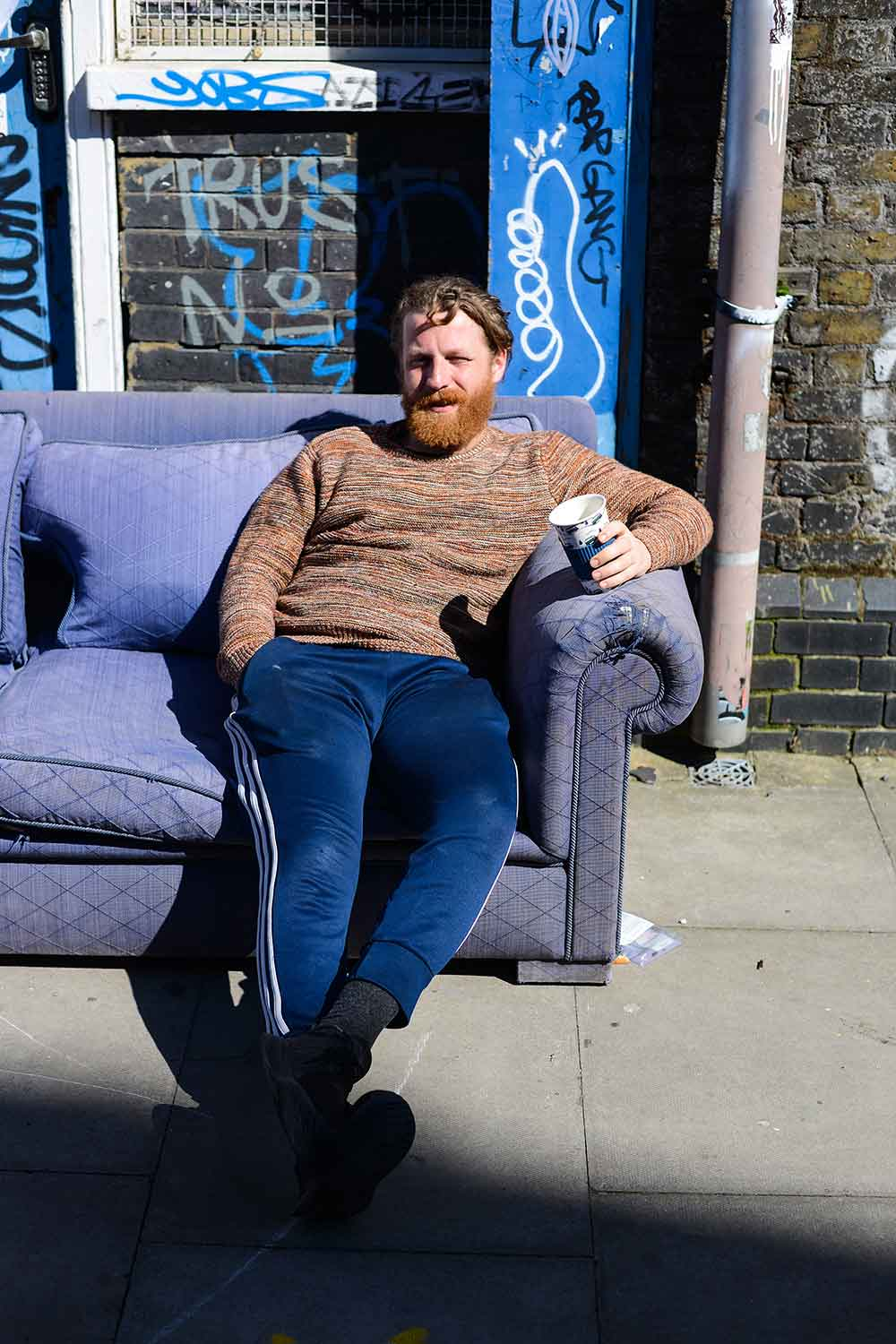 Man relaxing on a purple couch outside his home photographs of Bow in lockdown by Matt Payne
