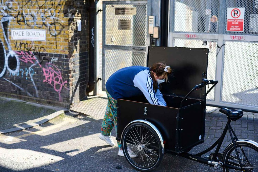 Woman in mask packing her bike trailer, photographs of Bow in lockdown by Matt Payne