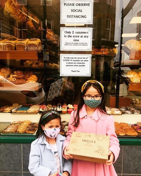 Two children outside of Percy Ingles Bakery holding boxed goods.