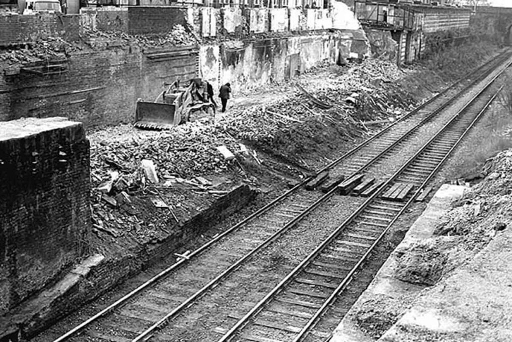 Black and white image of workers demolishing Bow Station and its railway in 1982