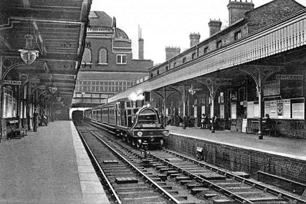 Black and white taken in 1904 image from Bow Station's platform, looking south towards the station and a steam train
