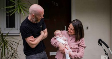 Couple with baby on doorstep smiling at baby environmental portraits Matt Payne