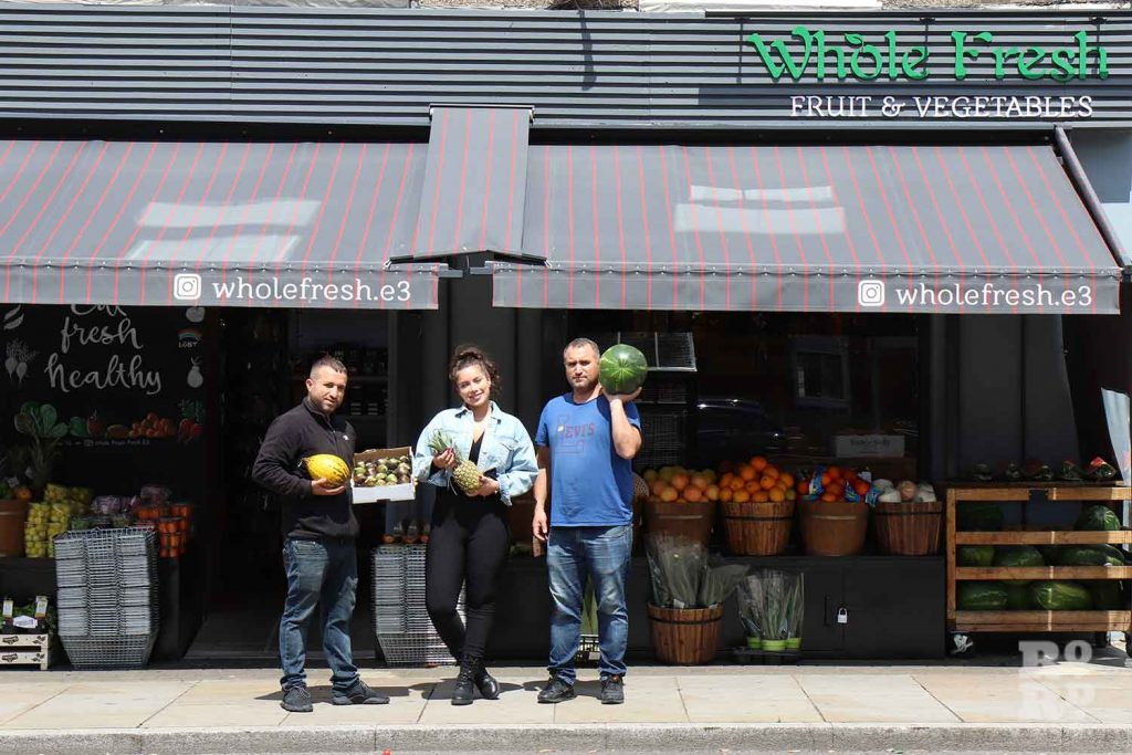 Owners of Whole Fresh standing outside their shop on Roman Road in Bow, East London