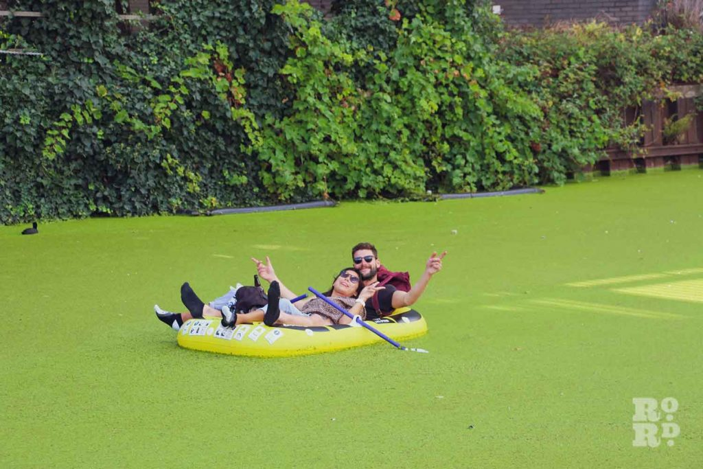 Couple on a dinghy on the Regents Canal, covered in pond weed
