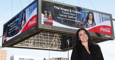 Owner of Angel and Crown pub, Melise Keogh, standing in from of the Coca Cola billboard featuring her business