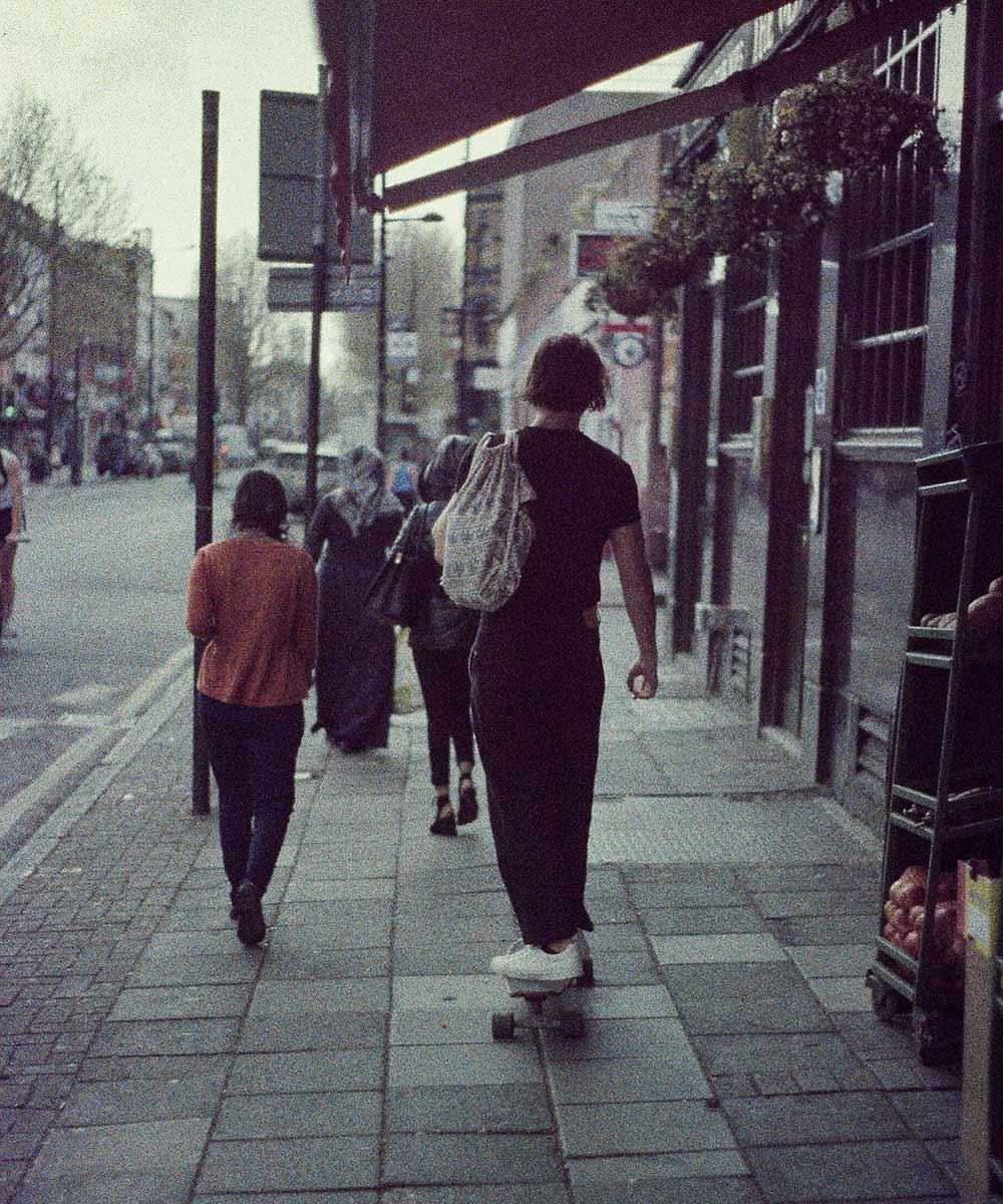 Woman skate boarding on pavement by Joseph Lockley