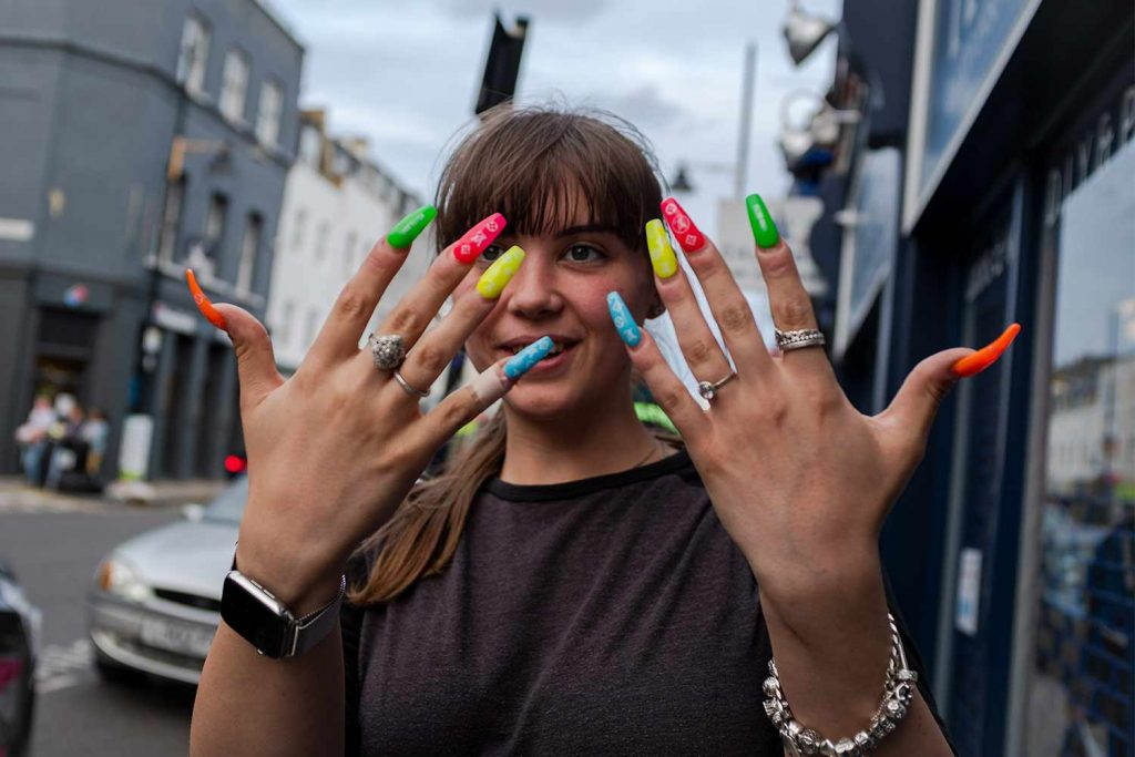 Woman on Roman Road holding up her colourful acrylic nails