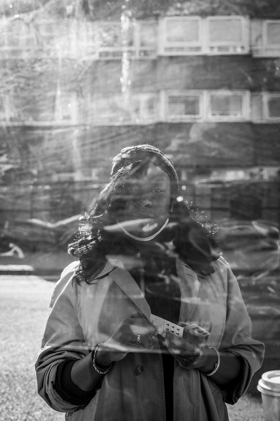 Black & white portrait of coffee shop customer through a window