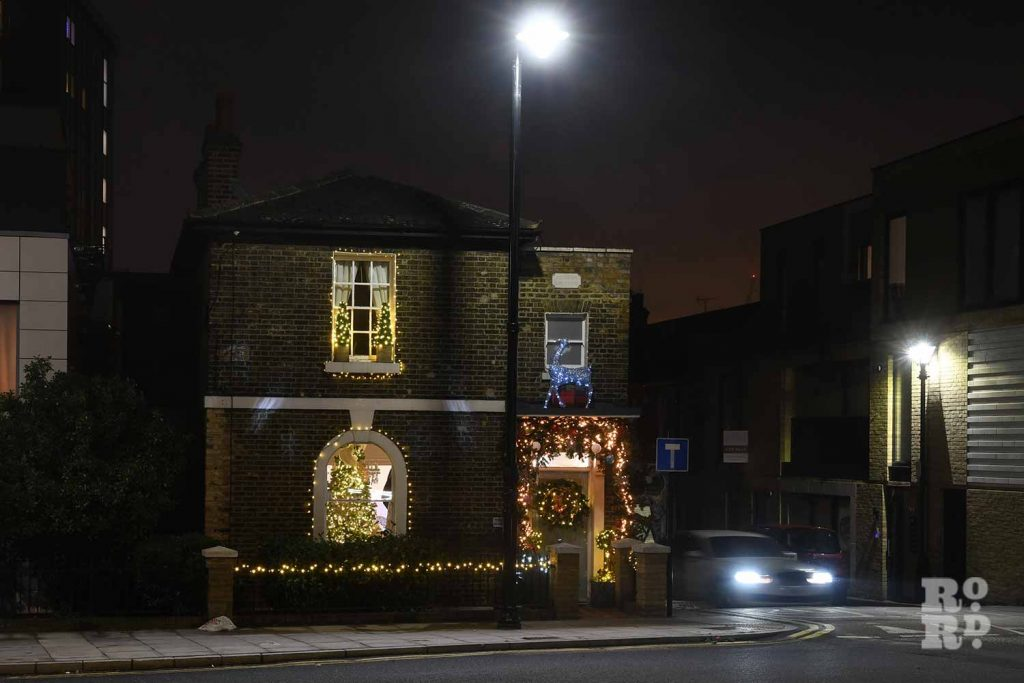 House in Bow decorated with traditional festive lights, by photographer Phil Verney