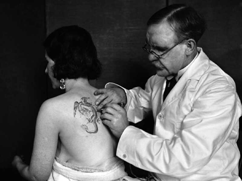 George Burchett, King of Tattooist, inking a dragon on woman's shoulder