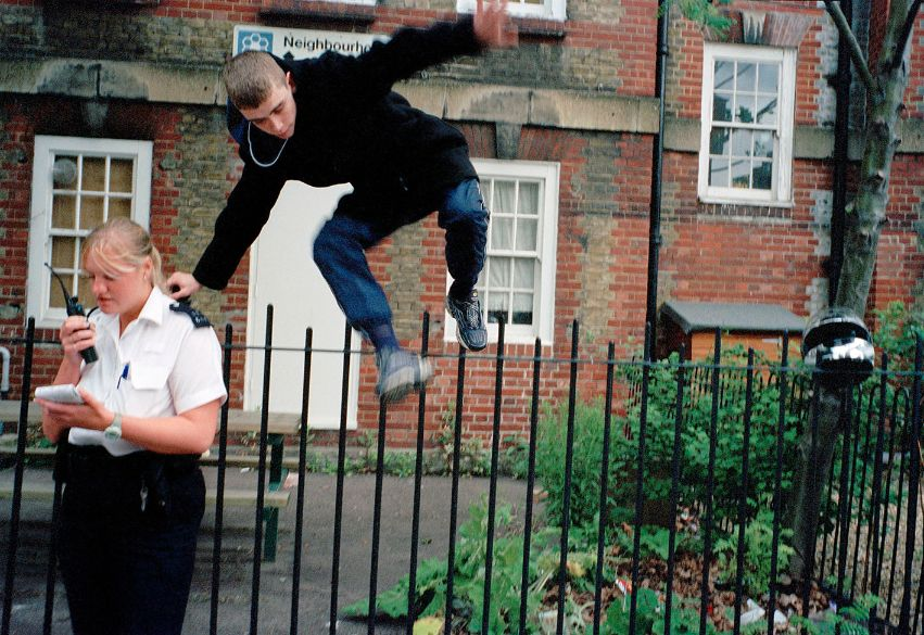 Young man jumping over railing next to police woman, by grime photographer Simon Wheatley