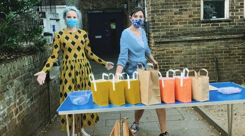 Two volunteers handing out food parcels at Neighbourhood Bites on Roman Road