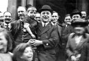 Labour MP George Lansbury in a crowd of people and holding a young boy