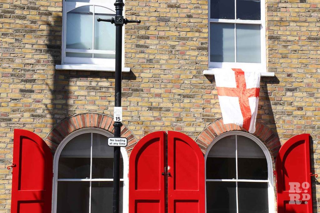 English flag flying from window above the bright red shutters of a house on Cyprus Street, Bethnal Green, East London.