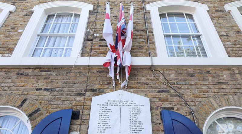 English and British flags over war memorial on Cyprus Street in Bethnal Green, East London.