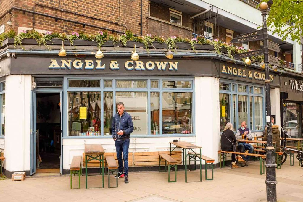 Patrons sit on benches outside Globe Town pub the Angel and Crown
