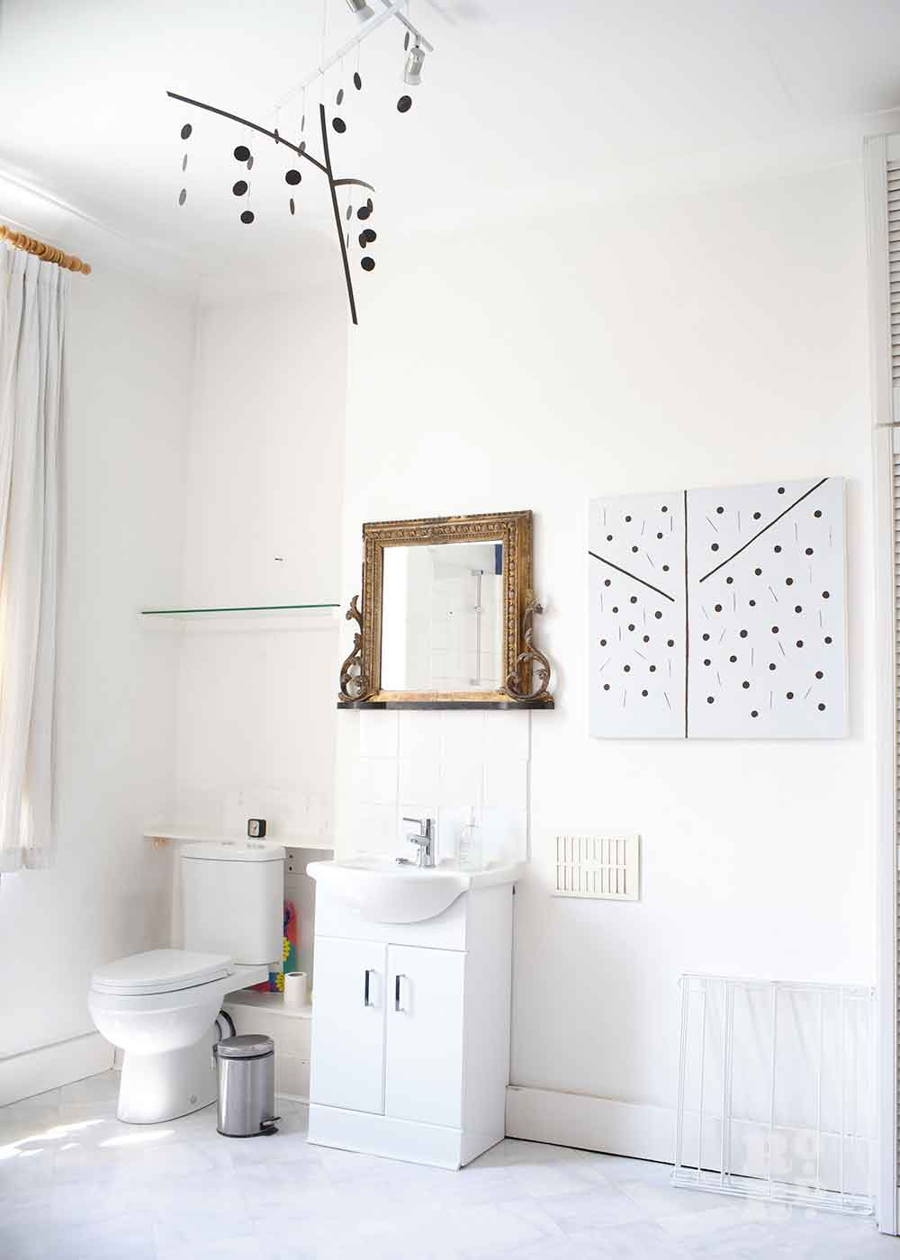 Art hanging in a white bathroom, the home of Bow artist Alice Sielle.