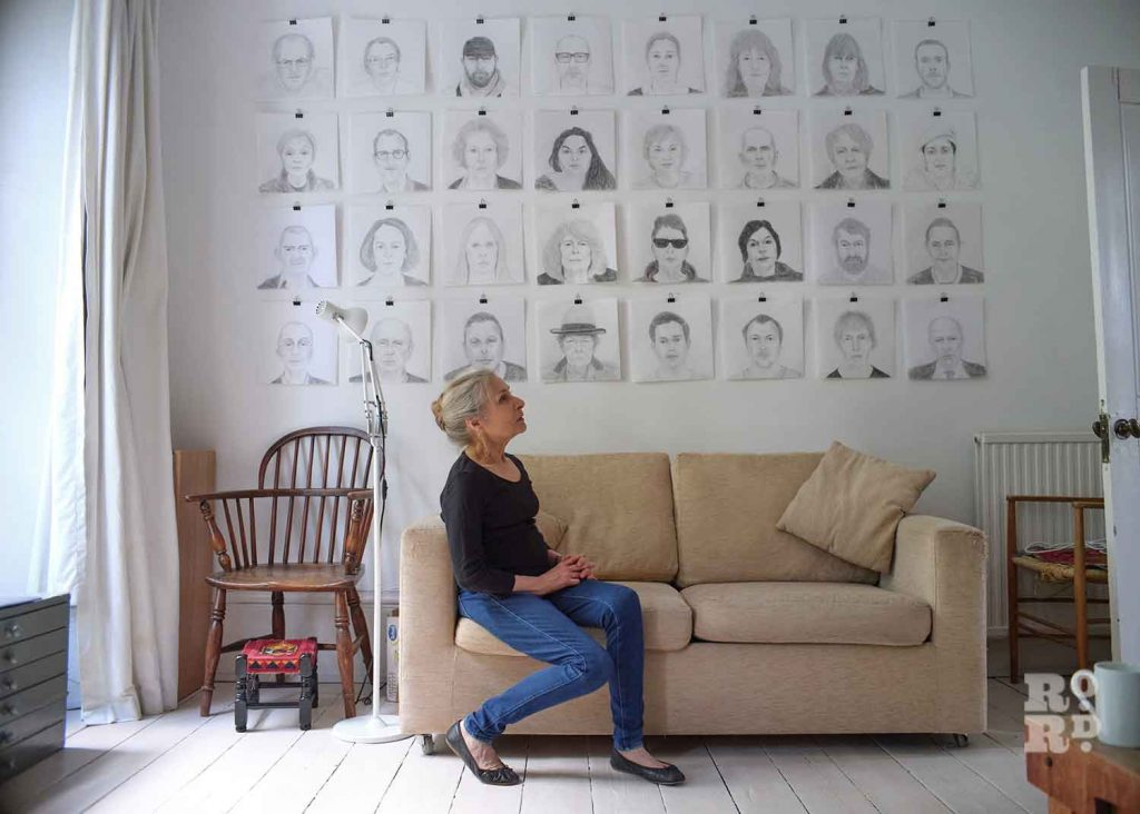 Alice Sielle and her wall of sketch portraits.
