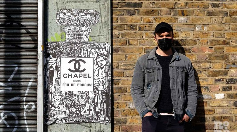 The artist known as Endless, standing next to his Chapel series of street art posters, Roman Road, East London.