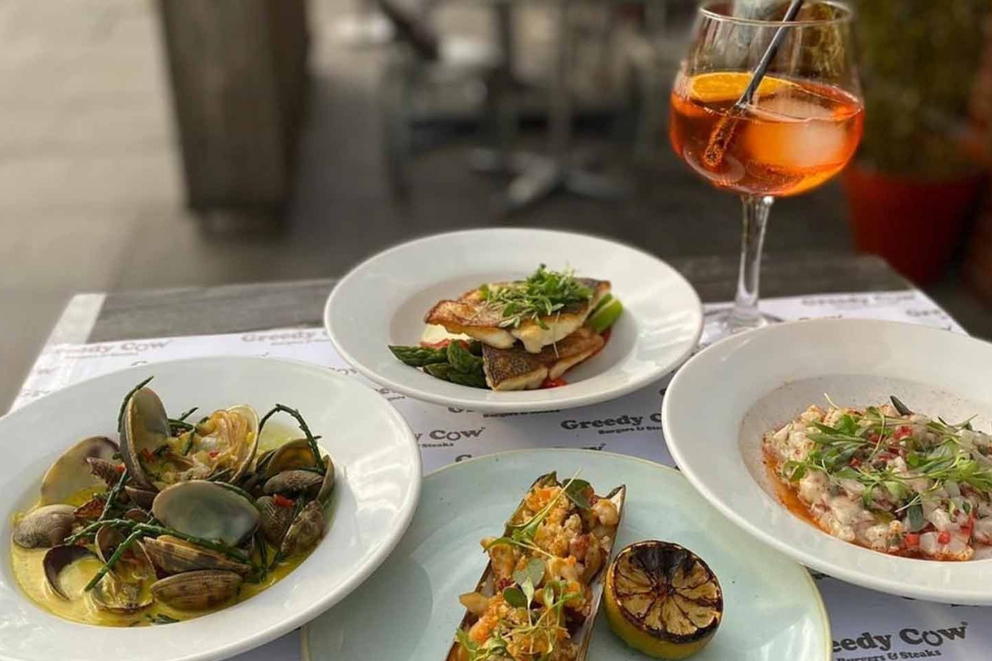 Four plates with a variety of fish dishes by Greedy Cow, with an Aperol Spritz in the background
