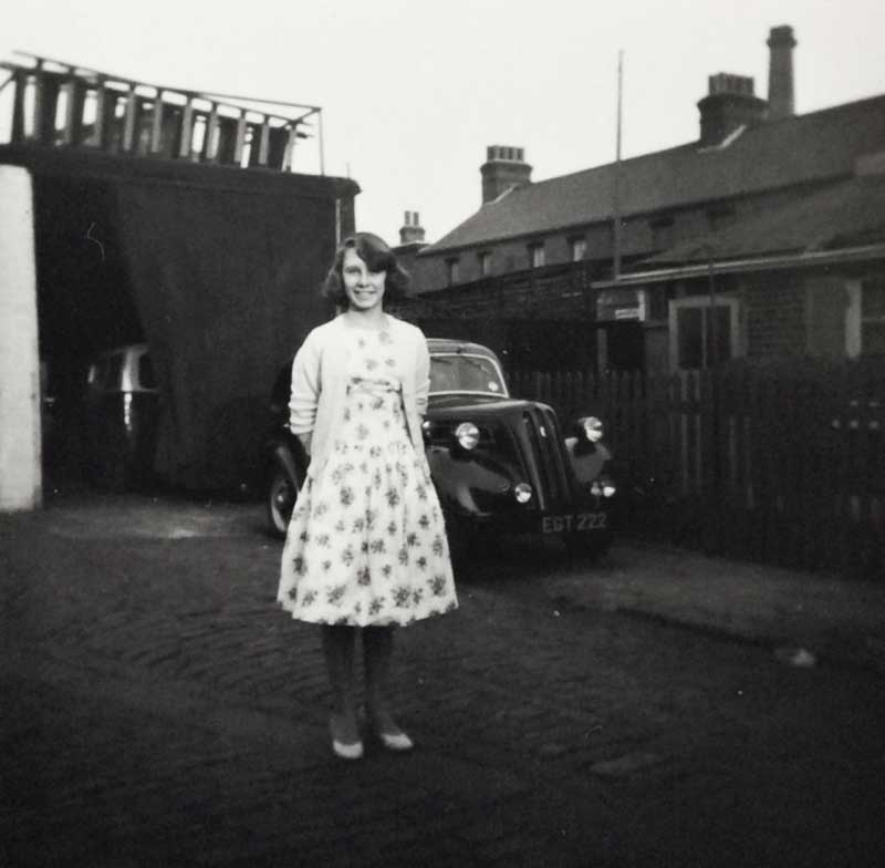Marian standing in the yard behind Pelican Cottage, Fairfield, Bow.