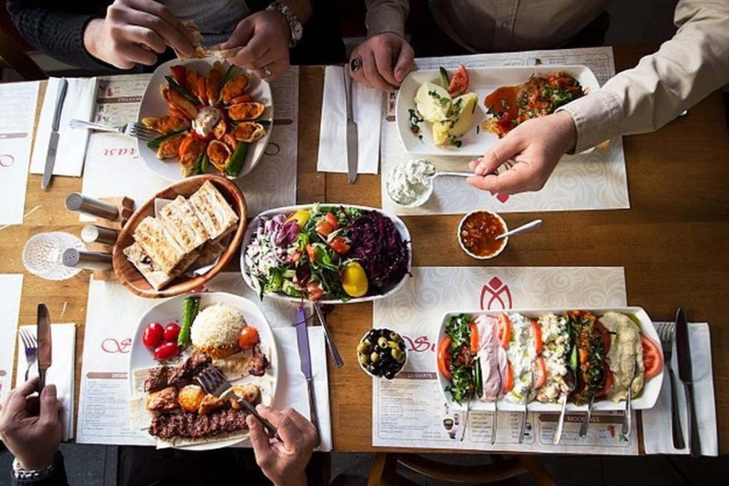 Three people eat a meal at Sultan Sofrasi; they're enjoying a variety of dishes plus olives and flat bread .