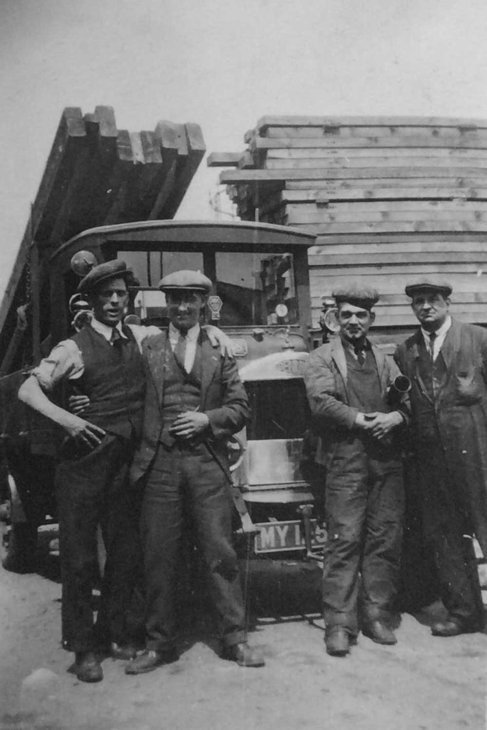 Workers standing in front of truck and wood supplies, Willaim Press Yard, Fairfield Road