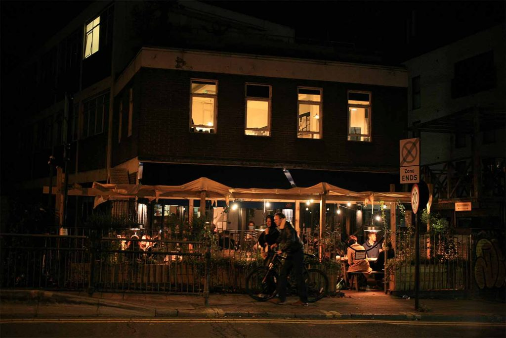 Two people leave Ombra after dark; the busy restaurant is illuminated by lights.