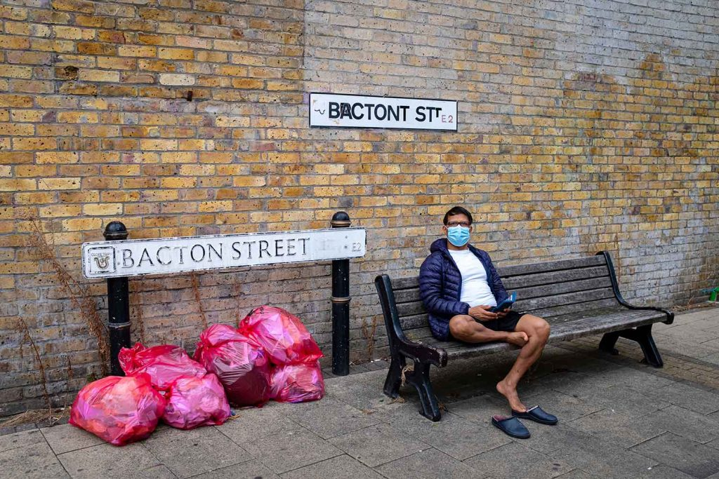 A man sits with his shows off next to the Bacton Street sign