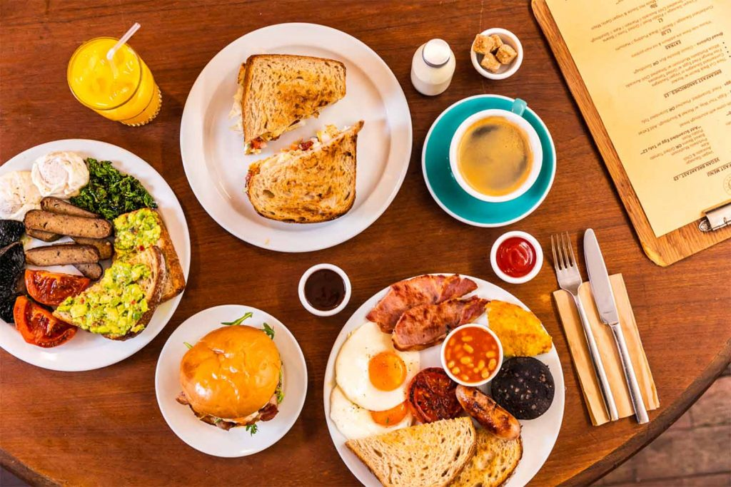 Fry-ups, breakfast sandwiches, avocado on toast and coffee sit on a table during brunch at Breakhouse Café