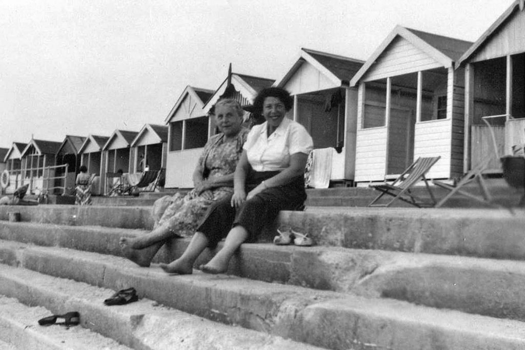 Two East End women sitting in front of the beach huts at Frinton in Essex, seaside holidays.
