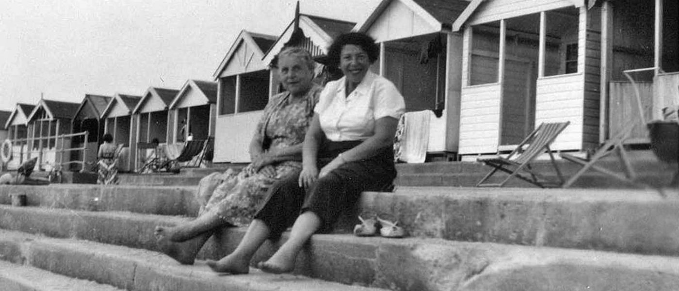 Two smiling women sit in front of a row of beach huts, their shoes off at Frinton Beach, East End seaside holidays