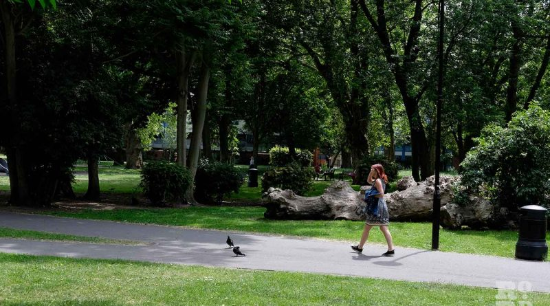 A woman strolls down a path through through Meath Gardens in East London