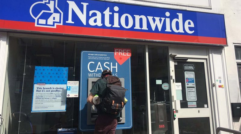 A man withdraws cash from the atm outside the Nationwide bank on Roman Road.