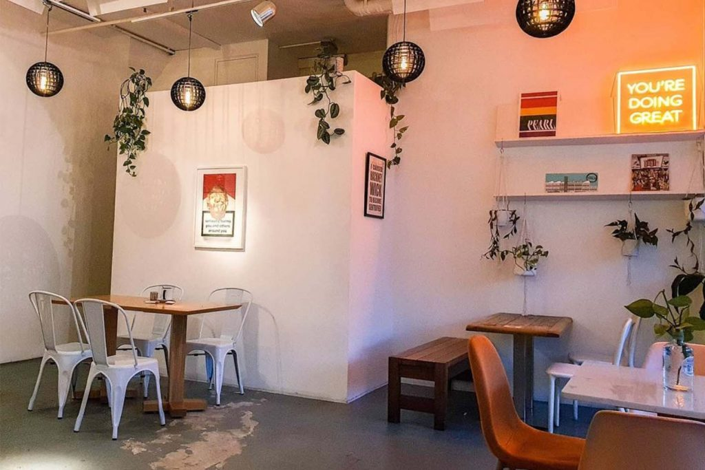 Chairs and tables sit in a warmly-lit corner of PEARL, Hackney Wick's favourite brunch spot