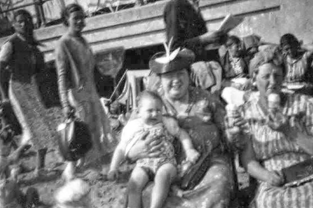 Two women sit on Ramsgate beach eating ice cream and holding a baby, a typical seaside destination