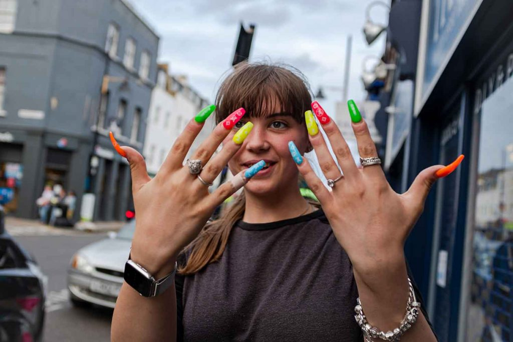 A woman sows off her long, brightly coloured nails outside a salon on Roman Road