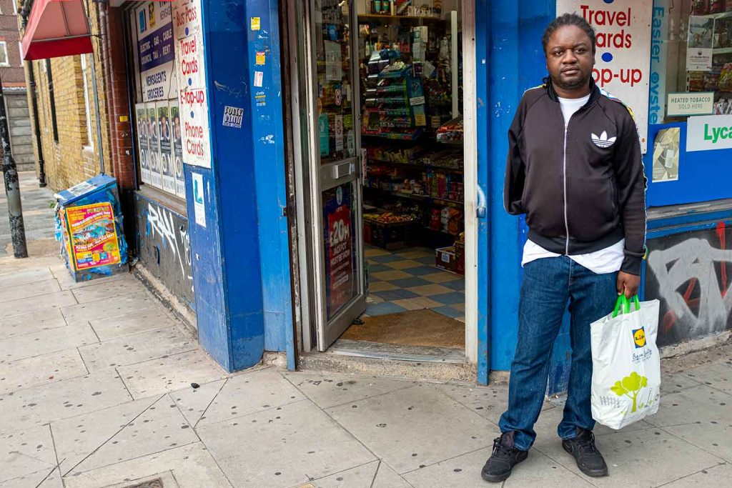 A man with one arm stands outside a corner shop near to Roman Road