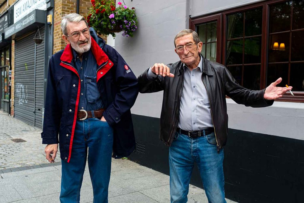 Two men bump elbows while smoking cigarettes outside The Albert pub