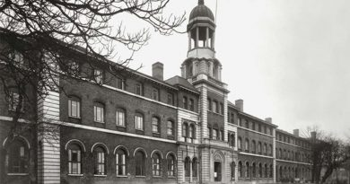 A black-and-white photograph of Stepney Union Workhouse on a grey, overcast day. Leafless trees in the foreground.