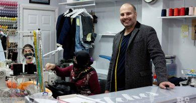 Mehmet Alpetkin stands at counter in Stitches; Hamiyet and Dilek sew behind him