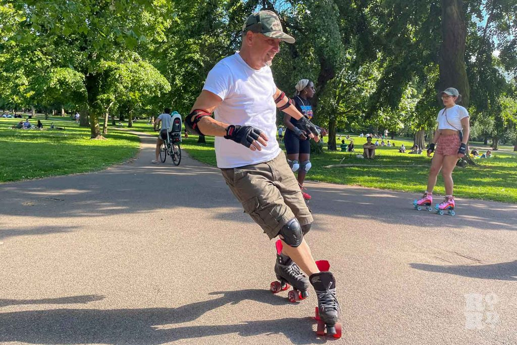 Roller skater with knee and elbow pads, Victoria Park, East London.