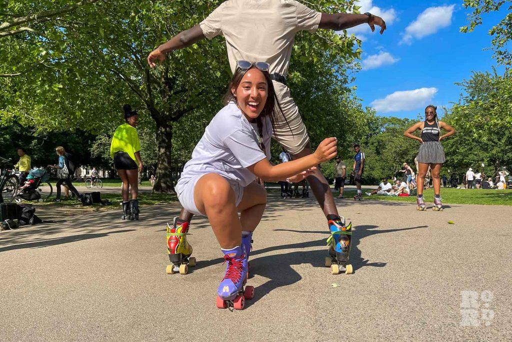 A roller skater skates through the legs another skater, Victoria Park, East London.