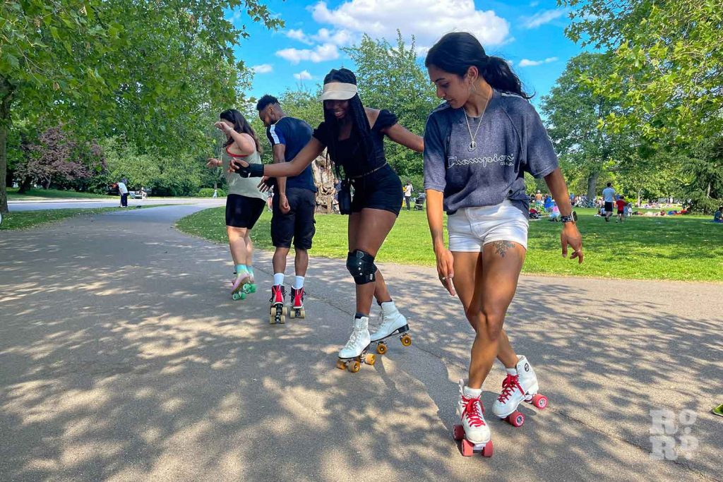 a line of roller-skaters moves, Victoria Park, East London.