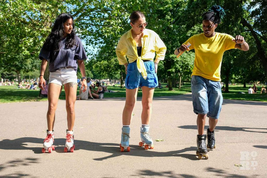 three skaters in a row watching an expert skater, Victoria Park, East London.