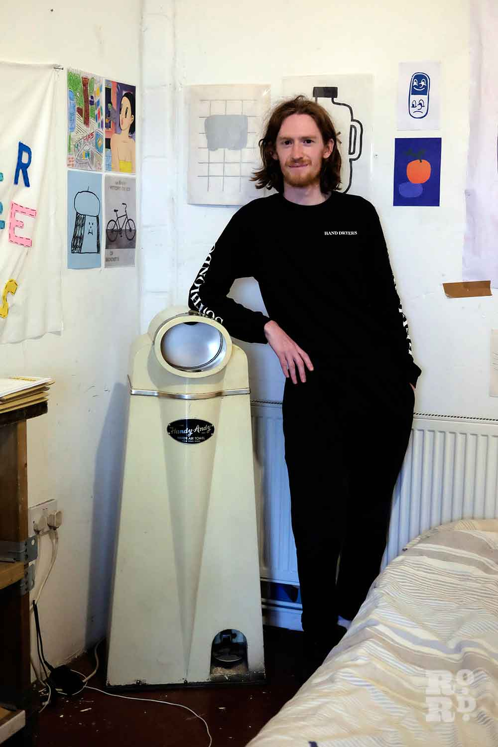 Artist Wedgley Snipes standing next to a vintage hand dryer.