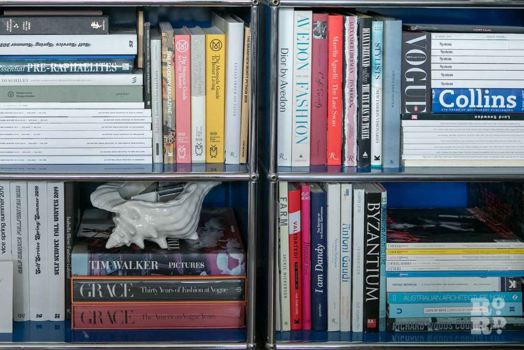 Bookshelves of coffee table books, stylist Wojtek van Portek in his Bow home.