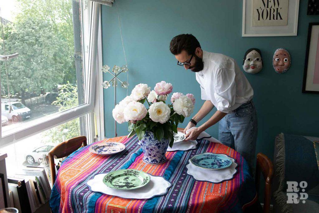 Setting the table, stylist Wojtek van Portek in his Bow home.